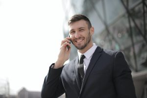 man-in-black-suit-jacket-holding-smartphone-3778680